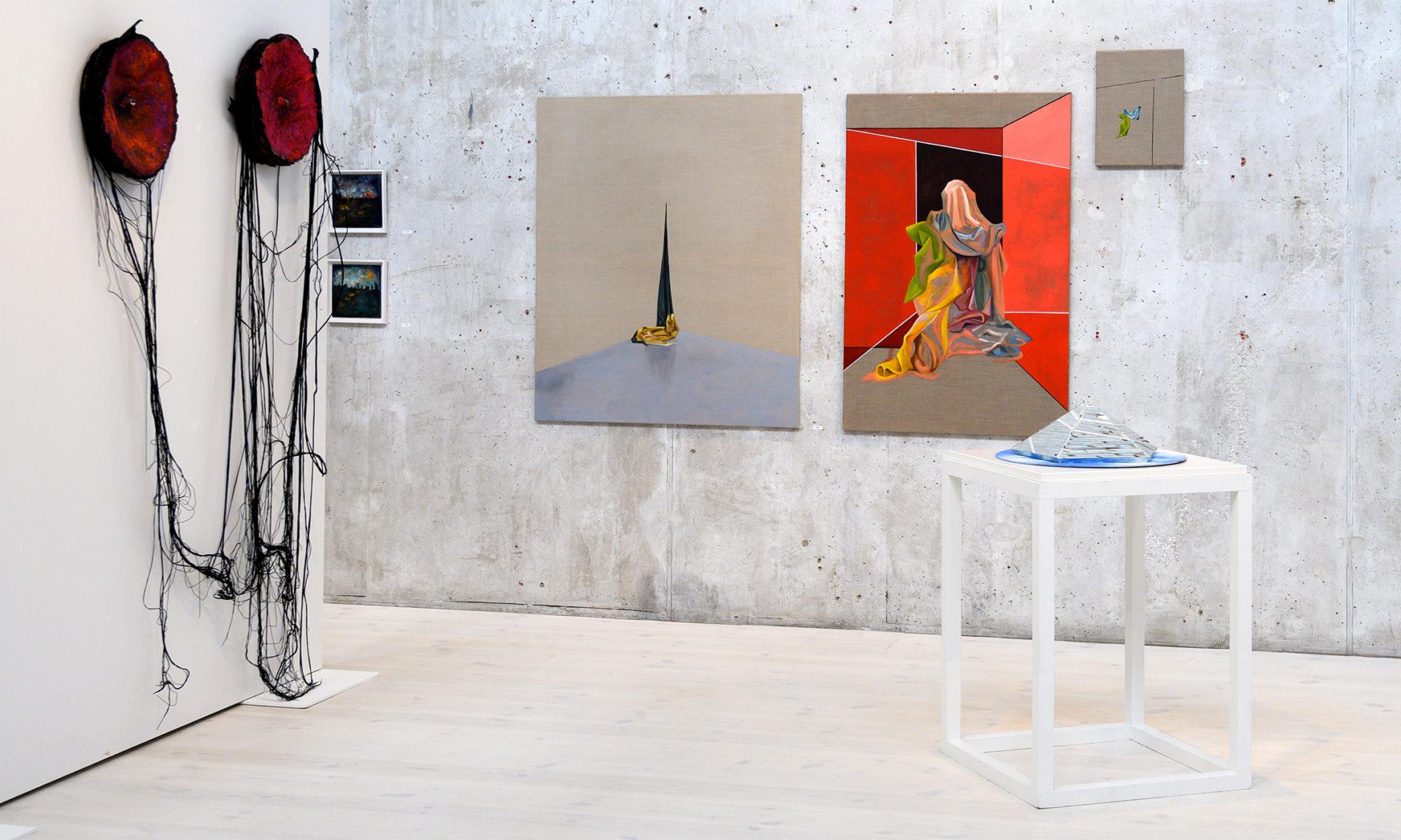 Delar av en utställningssal med konstverk i röda toner mot en grå betongvägg