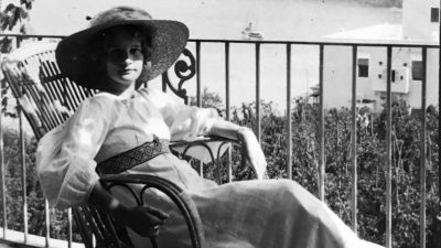 Svartvitt foto av Ester Bauer med solhatt, sittandes på en balkong/verande med utsikt över havet