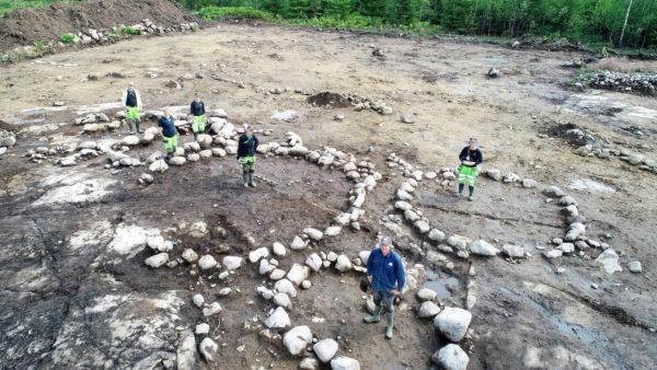 6 personer fotade uppifrån med drönare, står i ringar formade av stenar