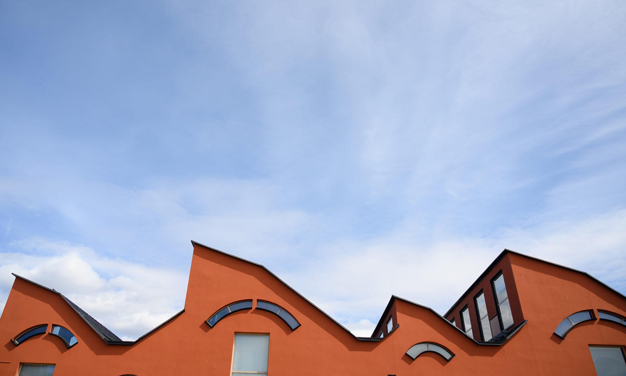 Museibyggnadens vågiga arkitektur i terracotta, mot en blå himmel med lätta moln