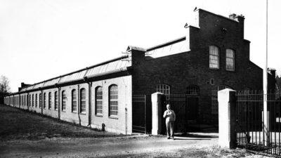 En svartvit bild av en äldre fabrik. En man står framför byggnaden.