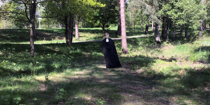 En ung kille klädd som präst