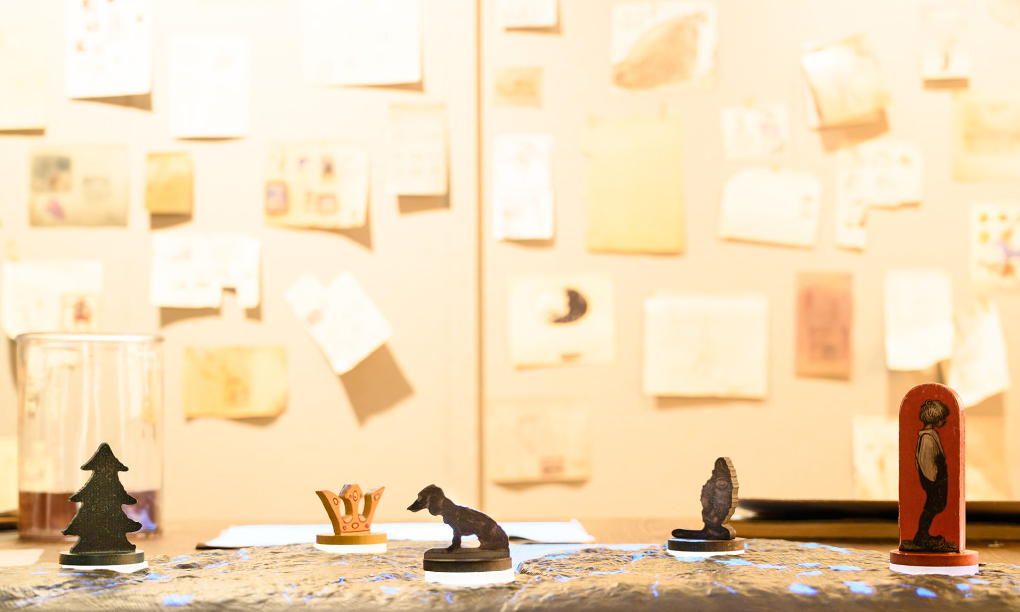 En ljus vägg med små skisser uppsatta i bakgrunden. I förgrunden små träfigurer i form av en krona, en gran, en prins, ett troll