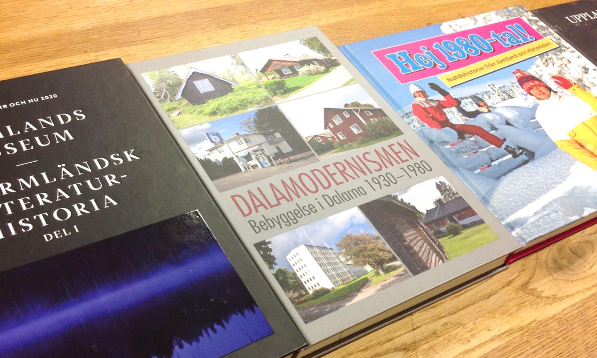 Fyra årsböcker från några länsmuseer ligger bredvid varandra på ett bord.