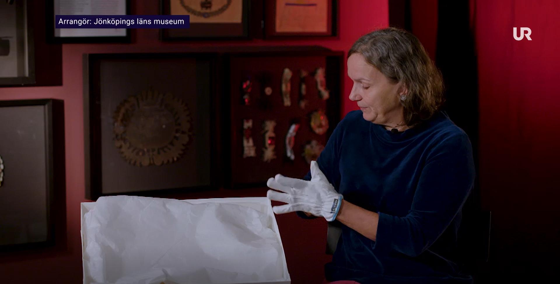 Utställningsproducent Katali Jarefjäll sitter med vita handskar på och ska visa ett föremål ur museets samlingar