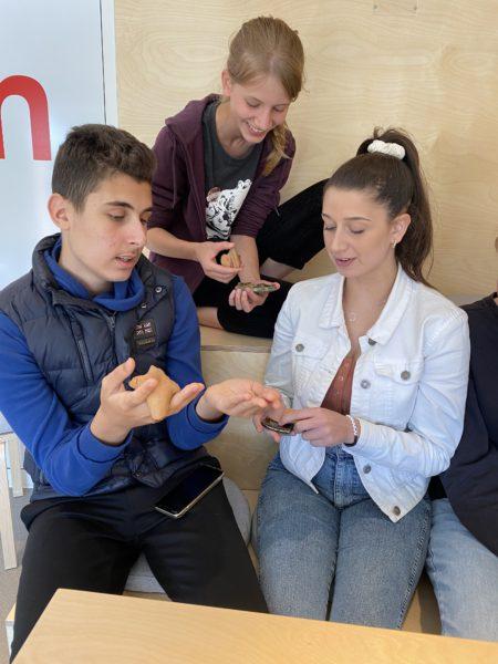 Tre ungdomar tittar på ett föremål tillsammans
