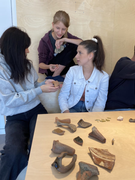 Tre tjejer kollar på ett föremål tillsammans
