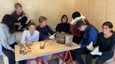 Ett gäng ungdomar sitter runt ett bord och kollar på äldre saker