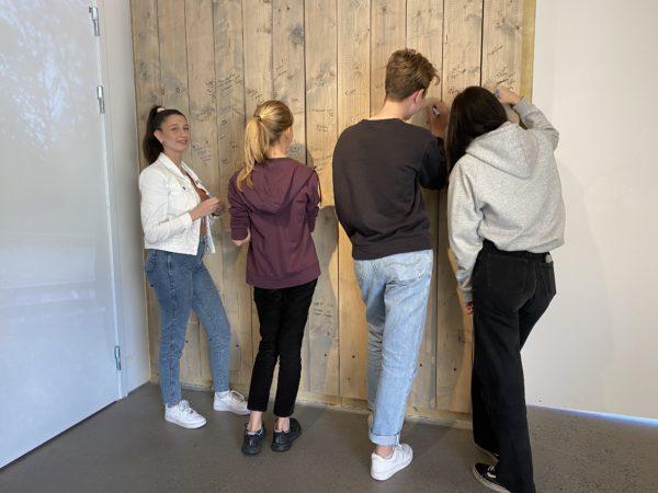 Fyra personer skriver på en vägg
