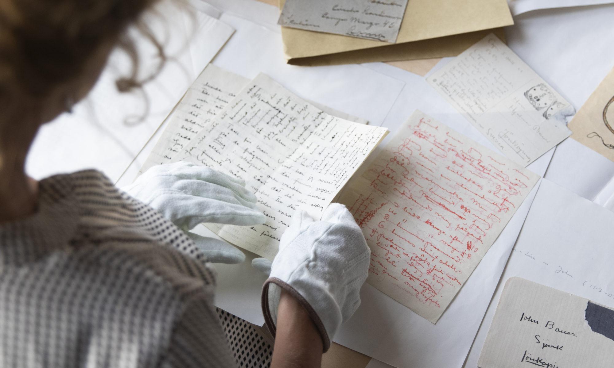 Äldre brev utspridda på ett bord. Person med handskar håller i ett av breven.