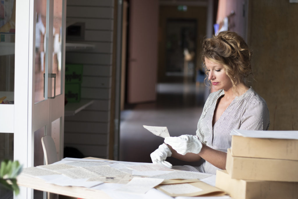 Kvinna sittandes vid ett bord fyllt med äldre brev