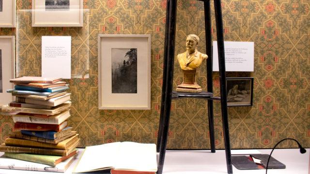 Foton och en statyett av Viktor Rydberg skymtar i utställningsmonter