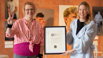 Två glada pedagoger som ler mot kameran och håller i den inramade utmärkelsen Årets pedagogiska pris