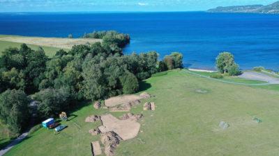 I en vy från ovan ser man den arkeologiska utgrävningen som ligger på en stor äng/slänt nära sjön Vättern.