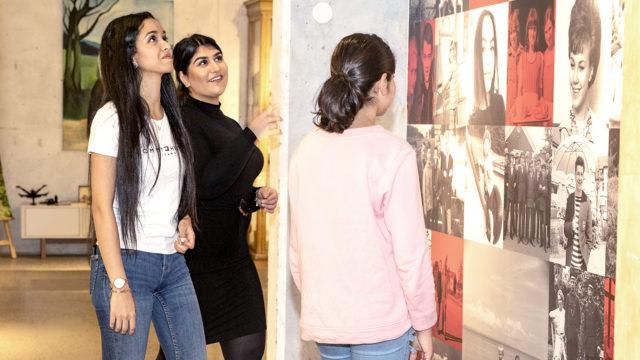 Tre unga tjejer står framför en vägg med porträtt