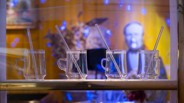 4 glasmuggar står på ett bord, i bakgrunden anas utställningsmiljön med porträtt och många detaljer