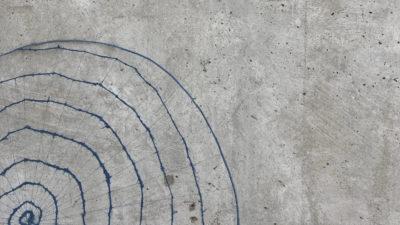 Ett skirt textilt konstverk av Ulrika Berge lutad mot en grå betongvägg