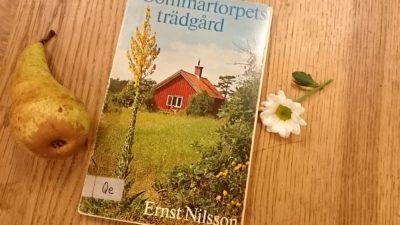 boken sommartorpets trädgård ligger på ett bord med en blomma och ett päron bredvid
