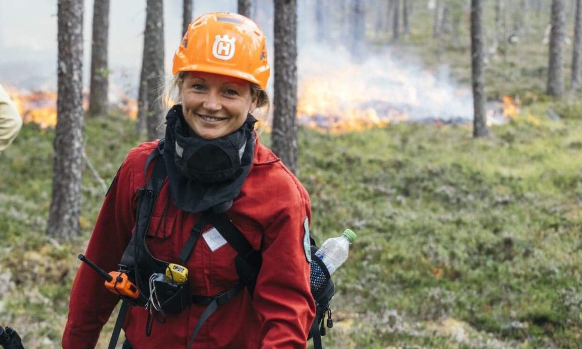 Porträtt av Annie Johansson ute i skogen, i bakgrunden ser man eldslågor och rök