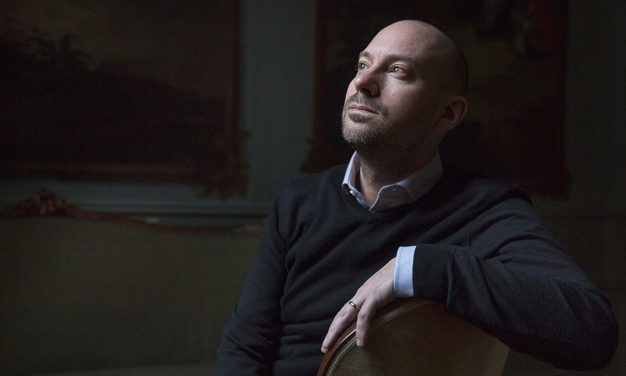 Porträtt av en man där bara huvud och ena handen syns, mot en svart bakgrund