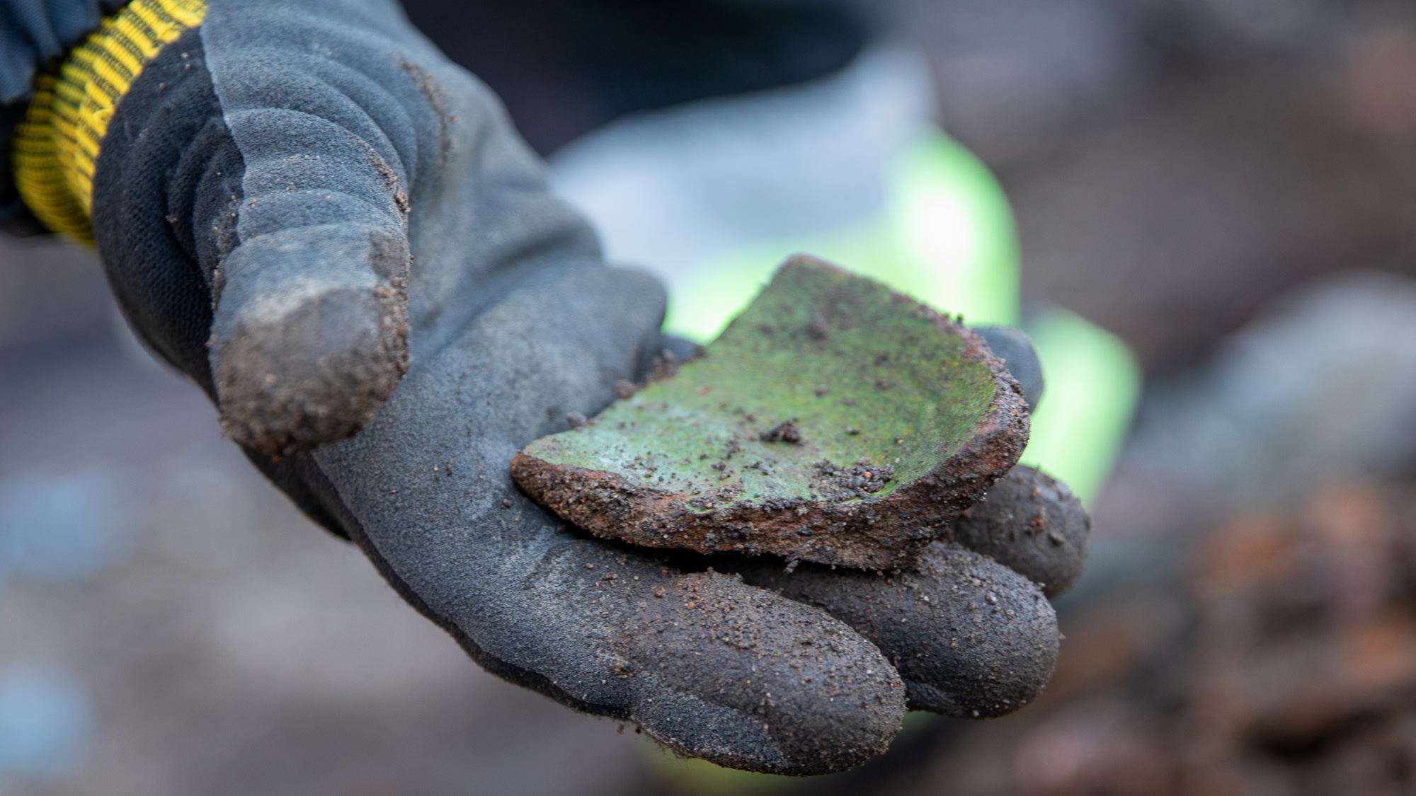 En hand med arbetshandske håller i en gröntonad krukskärva