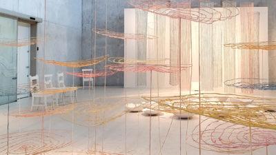 En utställningssal fylld med tunna, lätta skulpturer i tråd och metall