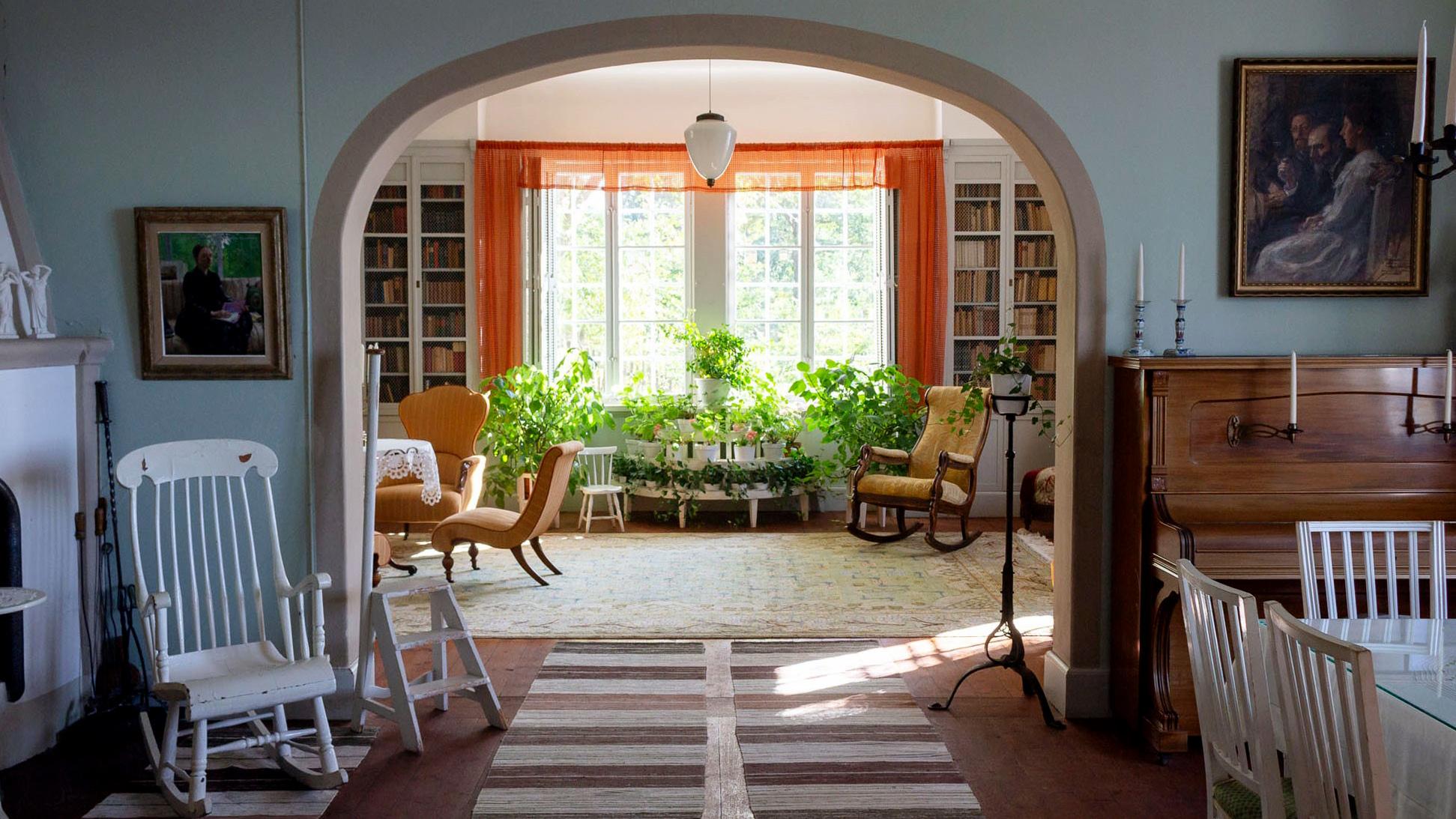 Ett stort rum med ett valv syns rakt fram, roströda gardiner och grönskande krukväxter i fönstret rakt fram. Trasmattor på golvet.