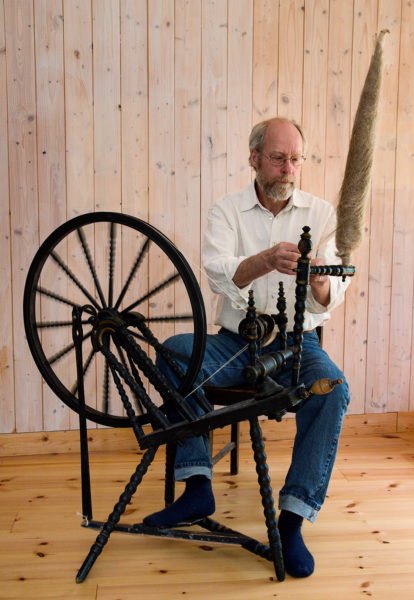 En man sitter vid en spinnrock och spinner