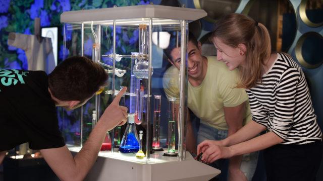 Tre ungdomar samlade runt en station i utställningen Kampen i Tiden