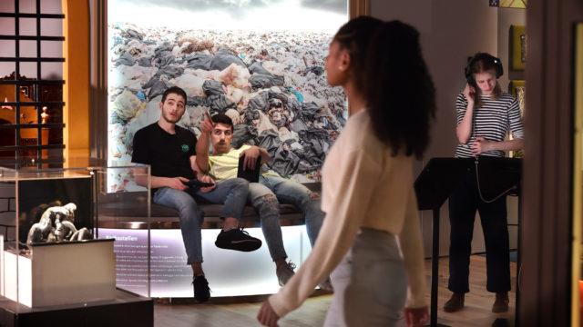 Två unga killar sitter på en bänk och pekar snett uppåt. En tjej går förbi i förgrunden. I bakgrunden en annan tjej som har hörlurar på och tittar på en skärm i utställningssalen.