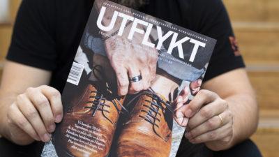 En person håller en tidskrift framför sig. Det står UTFLYKT och är en bild på en man som snörar på sig ett par bruna skor