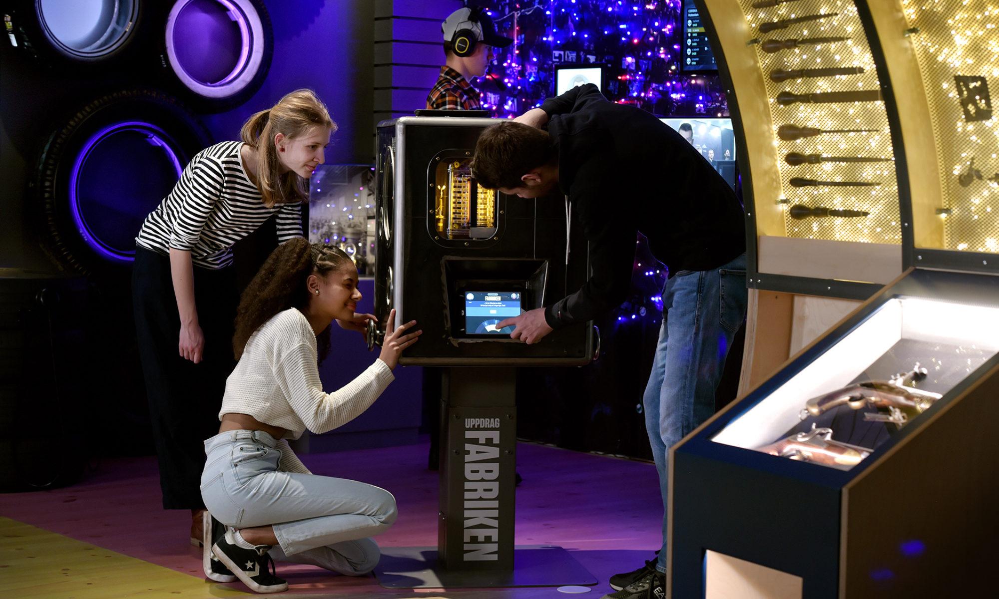 Tre ungdomar löser en utmaning vid en av de digitala stationerna i utställningen Kampen i Tiden. I bakgrunden lyssnar någon i hörlurar.